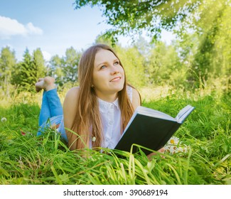 Beautiful girl in the meadow with a book