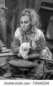 Beautiful girl mechanic repairing a car
