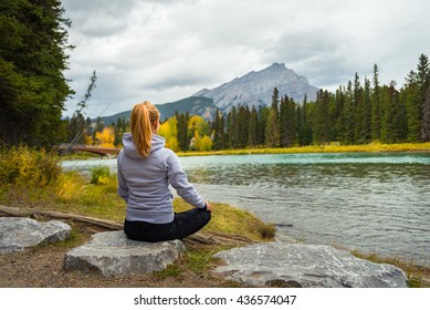 Beautiful girl meditating looking at the beautiful landscape