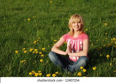 Beautiful girl meditation on meadow