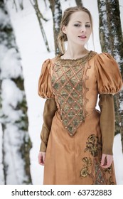 beautiful girl in middle aged costume in winter forest