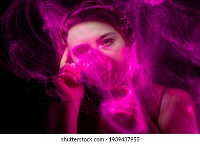 beautiful girl model with cosmic make-up on face, blue and purple color on dark background , longexposure foto