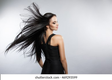 Beautiful girl model with developing the wind hair. A brunette woman in a black dress