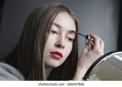 Beautiful girl model doing eyebrow makeup