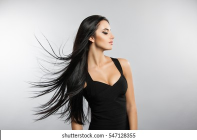 Beautiful girl model with flying the wind hair. A brunette woman in a black dress