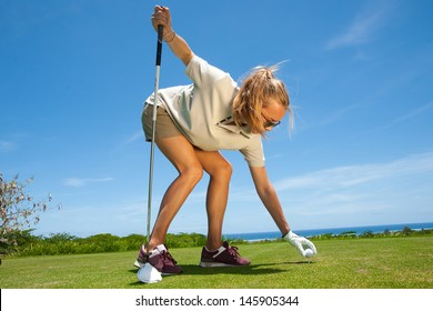 beautiful girl model with long blond hair playing golf in a sunny summer day on the island of Mauritius. golf course is located on the shore of the ocean