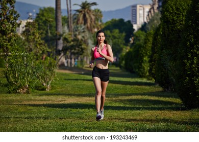 Beautiful girl model looks running on the green grass in the park
