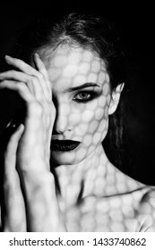 Beautiful girl model with red lips make up and naked shoulders covered with a shadow mask in the form of a net of hexagonal honeycomb. Close up. Black and white. Conceptual fashion design. Copy space