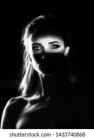 Beautiful girl model with red lips make up and naked shoulders in the shade, with a lit silhouette and a strip of light illuminating her eyes. Conceptual, art, fashionable design. Black and white.