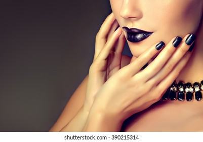 Beautiful girl  model showing black manicure nails . makeup and cosmetics