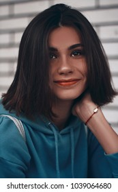 beautiful girl model smiling at the camera. portrait of a woman with short hair, brunette in blue hoodie.