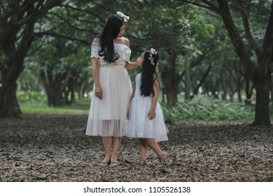 beautiful girl and mother in a park in Hanoi, Vietnam.