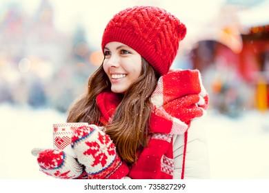 Beautiful girl with a mug outdoors