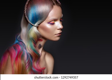 Beautiful girl with multi-colored hair and creative make-up and hairstyle. Beauty face. Photo taken in the studio