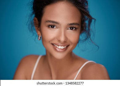Beautiful girl with naked shoulders, curly hair and nude make up smiling at blue background, perfect smile, portrait.
