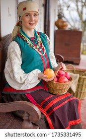 A beautiful girl in national dress is sitting. With apples in a basket. In old clothes of the 19th century. With a wreath and ribbons. Against the background of the ancient city. Village, countryside