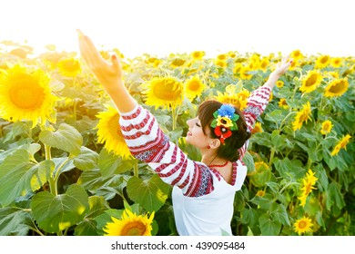 Beautiful girl in national ukrainian blouse embrodery rise hands up on a sunflower plant at sunset, backlight.