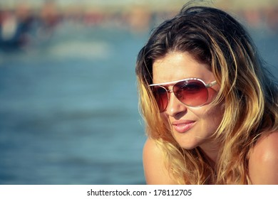 Beautiful girl natural looking retro color portrait outdoor enjoying  the sun by the sea - Young Caucasian woman fashion shoot by the sea
