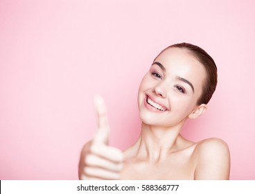 Beautiful girl natural makeup spa skin care on pink background with cute smile showing high five