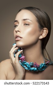 Beautiful girl with natural makeup and white nails and necklace with blue leaves. Fashion woman Portrait. Toned