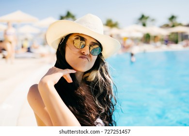 beautiful girl near the pool in a hat and sunglasses