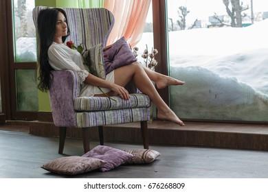 Beautiful girl near the window in the early morning
