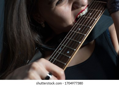 beautiful girl nibbles electric guitar fretboard. Close-up studio photo on a gray background.
