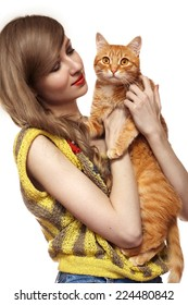 Beautiful girl in nice retro knitted sweater is holding ginger cat. Care about animals and love home pet.