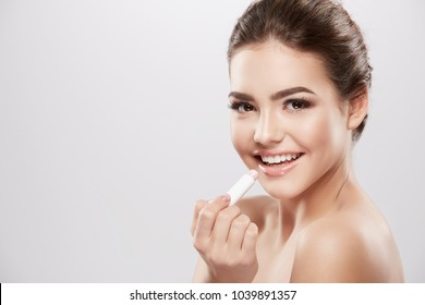Beautiful girl with nude make up and naked shoulders posing at grey background, skin care concept, beauty photo, close up portrait, using lipstick and smiling.