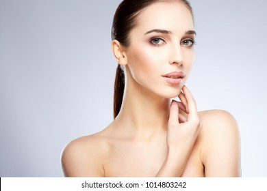 Beautiful girl with nude make up posing at grey studio background, beauty photo concept, looking at camera, perfect skin.