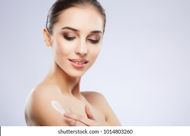 Beautiful girl with nude make up posing at grey studio background, beauty photo concept, perfect skin, using skin cream.