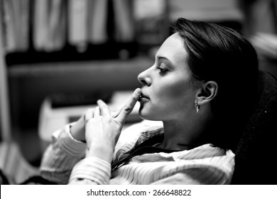 Beautiful girl in the office sitting in a chair and thinks about something