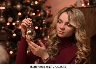 Beautiful girl on the background of a New Year tree.  New Year. Christmas tree toy in the hands. Silver ball. Turtleneck. Garland.