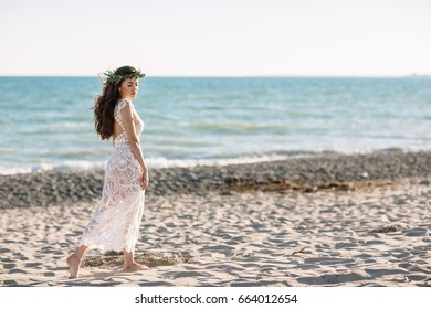 Beautiful girl on the beach in a beautiful dress. Sunny day, white sand, boho.