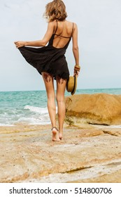 Beautiful girl on big rocks correct her little black summer dress flying in the wind. View from back. Beauty cute girl on a tropical beach sea ocean shore with large stones. Outdoor summer lifestyle.