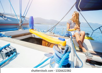 Beautiful girl on board of sailing yacht on summer cruise. Travel adventure, yachting with child on family vacation. Kid clothing in sailor style, nautical fashion. Focus on the Sailboat winch