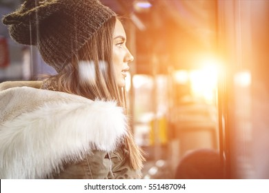 Beautiful girl on a bus looking outside the window - Stunning young woman in winter clothes - Trend concept - Warm filter