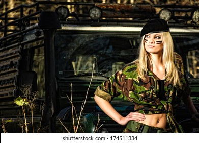 Beautiful girl on camouflage outfit, off-road vehicle behind