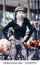 Beautiful girl on carousel amusement ride at the park. Fashion photo