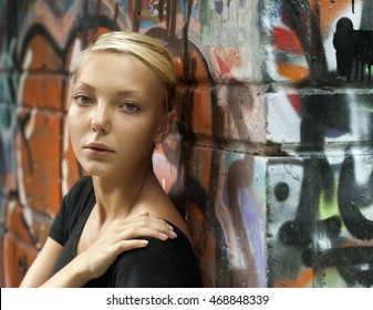 beautiful girl on a city street near a wall of graffiti