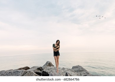 0ef94710236d A beautiful girl on the edge of the earth near the sea or ocean sits on