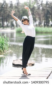 Beautiful girl on a fishing bridge in the park. Wearing a hat, white shirt and black pants. Cheerful mood and smile.