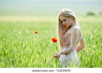Beautiful girl on green field with poppies in spring