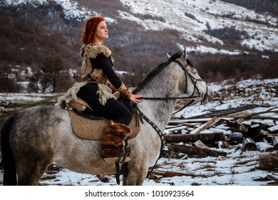 Beautiful girl on horse and with red hair in armor. Woman is a Viking. Fantasy