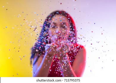 Beautiful girl on party background blowing confetti