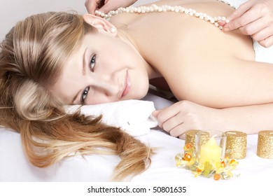 beautiful girl on procedure of massage by pearls