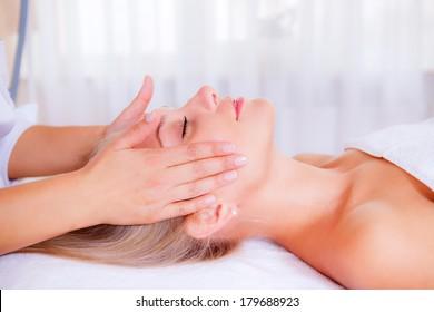 beautiful girl on reception at the masseur. facial massage, closeup