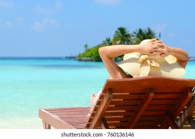 Beautiful girl on sunbed relaxing  at tropical  Maldives island. Travel and Vacation.