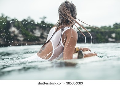 Beautiful girl on a surf board in the ocean. Girl with long hair in a white bathing suit in the ocean on the longboard. beautiful girl with a tattoo on his back in the ocean surf.