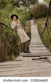 Beautiful girl on a suspension bridge. Woman in a black hat and a beige trench coat. Pretty girl on the suspension bridge. Fashionable autumn woman. Girl in black leather boots.